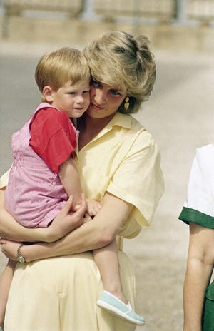 The Princess of Wales holds son Prince Harry while royal families posed for photographers at the Royal Palace, Majorca, Spain on Sunday, August 9, 1987.