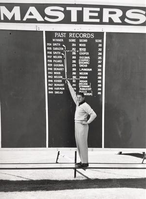 Horton Smith, the first Masters Tournament champion, poses at the scoreboard in later years.