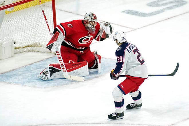 Oliver Bjorkstrand scores the winning goal for the Blue Jackets in the fourth round of a shootout Saturday night, beating Hurricanes goaltender James Reimer for a 3-2 victory in Raleigh, N.C.