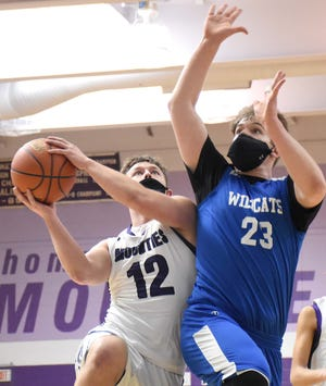 Little Falls Mountie Rikki Smith goes up for a shot in the first quarter with Brandon Dunckel defending for Owen D. Young Saturday, March 20, 2021, in Little Falls, New York.