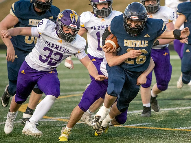 Knoxville junior running back Brayden Wall, right, breaks through the line as Farmington's Jacob Johnson gives pursuit during the Blue Bullets' 20-14 season-opening loss to the Farmers on Saturday, March 20, 2021 at Van Dyke Field in Galesburg.