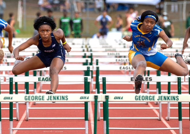 McKeel eighth-grader Chelsi Williams and Auburndale senior Tyra Thomas race neck-and-neck in the 100 hurdles on Saturday at the George Jenkins Classic. Williams won in 14.25 seconds to Thomas' 14.28 seconds.