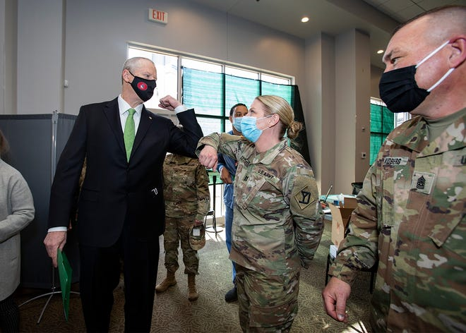 Gov. Charlie Baker elbow bumps Massachusetts National Guard Captain Wendy Letchworth of Maine during a tour of the COVID-19 vaccination site at The Shaw's Center in Brockton last month.