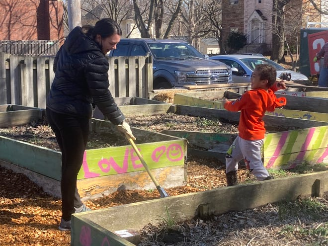 Micah Schmidt, 5, stomps down mulch that his mom, Malia Schmidt, rakes at Douglas Avenue United Methodist Church's community garden Saturday. About 15 or so people took part in the work day readying the garden's 17 planting boxes. Community members can rent them for the season for a $10 suggested donation. [Steven Spearie/The State Journal-Register]