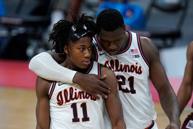 Illinois center Kofi Cockburn (21) talks with Illinois guard Ayo Dosunmu (11) after a foul against Loyola Chicago during the second half in the second round of the NCAA tournament at Bankers Life Fieldhouse in Indianapolis, Sunday. (AP Photo/Paul Sancya)