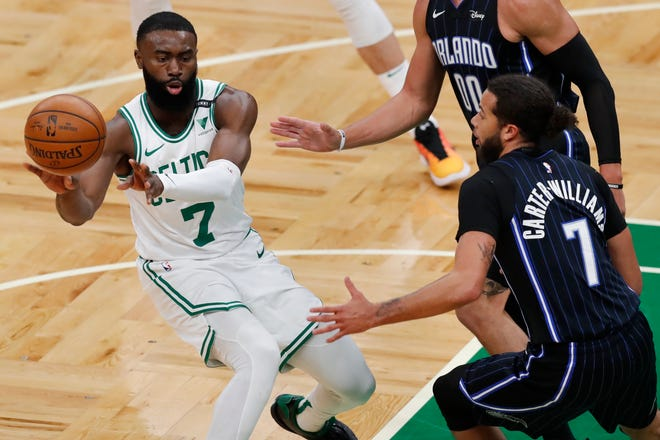 Boston's Jaylen Brown, left, passes off against Orlando's Michael Carter-Williams during the first half of Sunday's game.