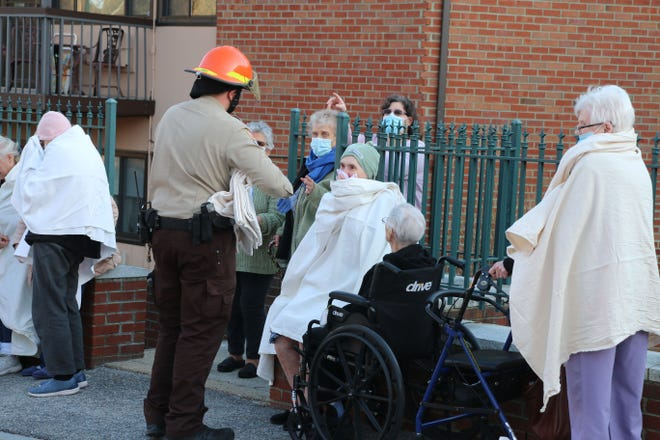Colony Retirement Homes residents huddle outside after being evacuated from their homes by Worcester fire and EMS crews after a blaze broke out in one of units Saturday.
