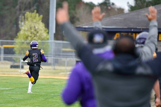 Jack Britt's sideline celebrates after Tyler Williams scores a touchdown after his interception return.