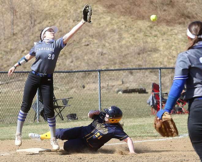 Kent State University Tuscarawas softball's Cassy Donaldson slides into third base safe as Ava Scott of Lakeland Community College  reaches for the throw  in the first game of a doubleheader Sunday.