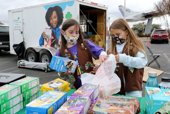 Gaby Sloss loads cookies into a bag held by Sophia Milam at a Girl Scout drive-through cookie sales event Friday, March 19, 2021, at the Tuscaloosa Veterans Memorial Park. [Staff Photo/Gary Cosby Jr.]