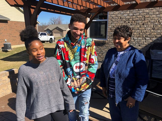 Brilee Carter, left,13, and Cobe Calhoun, 17, share a laugh with their great-grandmother, Doris Rolark, outside Rolark's daughter's home on March 7, in Monroe, Ohio.
