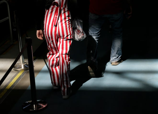 A Wisconsin fan wearing the iconic candy-striped overalls walks through Hinkle Fieldhouse for the Badgers' game against Baylor during the second round of the 2021 NCAA Division I basketball tournament in Indianapolis, Indiana, on Sunday, March 21, 2021.