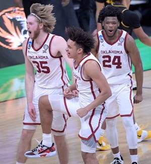 Oklahoma Sooners forward Brady Manek (35), Oklahoma Sooners forward Jalen Hill (1) and Oklahoma Sooners guard Elijah Harkless (24) celebrate after defeating Missouri during the first round of the 2021 NCAA Tournament on Saturday, March 20, 2021, at Lucas Oil Stadium in Indianapolis, Ind.