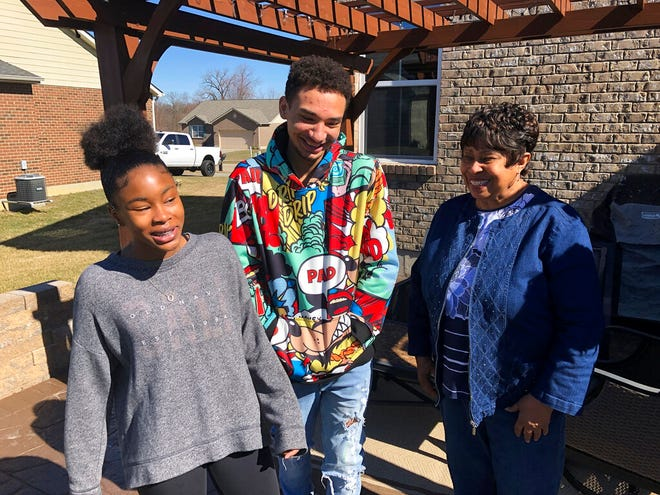Brilee Carter, left,13, and Cobe Calhoun, 17, share a laugh with their great-grandmother, Doris Rolark, outside Rolark's daughter's home on March 7, 2021, in Monroe, Ohio. The pandemic and its isolating restrictions have been especially tough for many of the nation's some 70 million grandparents, many at ages when they are considered most vulnerable to the deadly COVID-19 virus. Rolark, of Middletown, Ohio, has always been active with the offspring. She raised three children mostly on her own, had five grandchildren (two now deceased), and has helped a lot with some of her 16 great-grandchildren. (AP Photo/Dan Sewell)