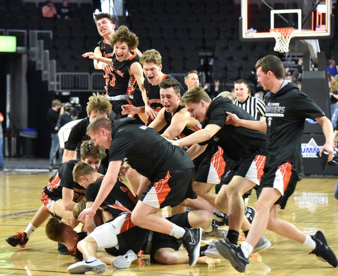 Dell Rapids players swarm the court to celebrate Landon Ruesink's 3-point buzzer beater against No. 1 Vermillion in the opening round of the South Dakota State Class A Boys' Basketball Tournament in Sioux Falls on March 18, 2021.