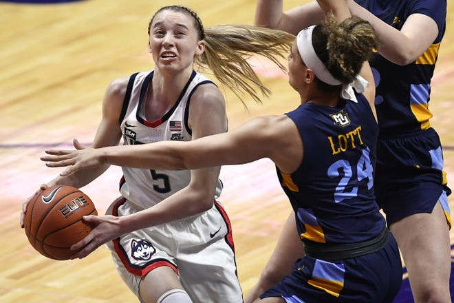 Connecticut's Paige Bueckers, driving to the basket in a Big East Tournament game against Marquette, leads the Huskies with 19.9 points a game.