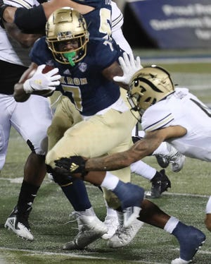 Akron's Teon Dollard wards off a Western Michigan defender on a carry during a game in November at  InfoCision Stadium.