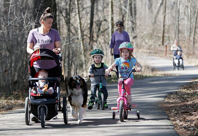 Tiffany Arnold enjoys a walk Monday on the paved trail with her children Boone (in stroller), Lane and Ella along with their dog, Bo, at Freer Field.
