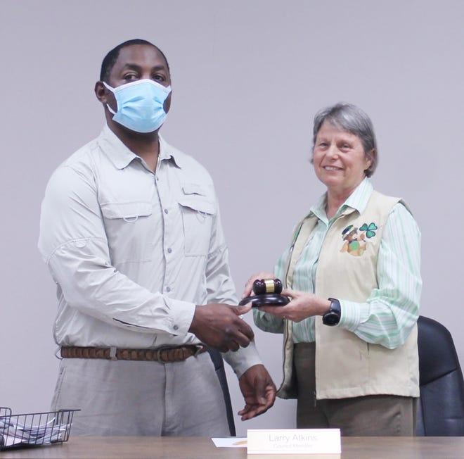 Mayor Pro Tem Larry Atkins hands the mayor's gavel to newly elected Jenny Smith.