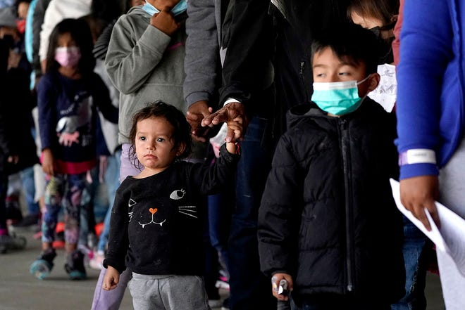 Migrant children are seen with adults as they wait in line to get a COVID-19 test before given travel instructions at a bus station, Wednesday, March 17, 2021, in Brownsville, Texas. A surge of migrants on the Southwest border has the Biden administration on the defensive.
