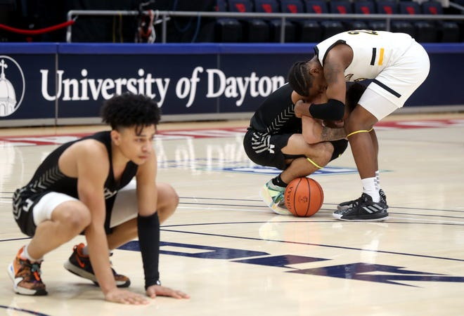 Jayson Hayes of Centerville consoles Westerville Central's Tasos Cook after the Elks edged the Warhawks 43-42 in Sunday's Division I boys basketball state championship game. Central's Quincy Clark is in the foreground.