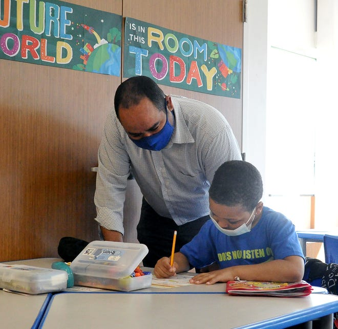 """Josh Nolan,  Orrville Area Boys and Girls Club executive director, helps 8-year-old Keyvon Redd with his homework during the """"power hour"""" time Monday after school."""