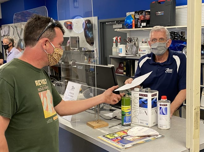 Rick Emerson, one of the owners of Ben's Paint Supply in Daytona Beach, works with customer Tim Day recently. Ben's Paint Supply was one of thousands of Volusia and Flagler county businesses that used federal Paycheck Protection Program loans to continue paying employees through the pandemic.