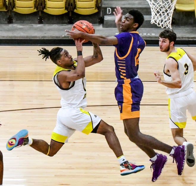 Garden City Community College's Rodney Lewis, left, drives the lane for a basket but is fouled by Dodge City's Quindarius Thomas in the process, sending Lewis to the free throw line Saturday at Perryman Athletic Complex.