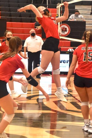 Charger Abby Watson, center, winds up for a hit during the varsity match with the Riverdale Rams on Tuesday, March 16, in Orion.