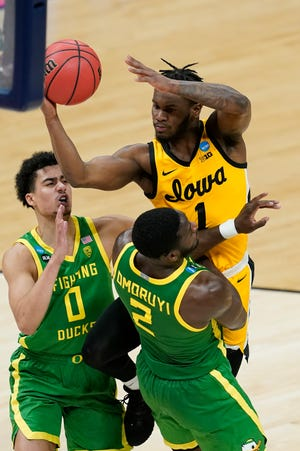 Iowa's Joe Toussaint (1) is called for charging against Oregon's Eugene Omoruyi (2) during the second half of Monday's second-round game in the NCAA tournament at Bankers Life Fieldhouse.