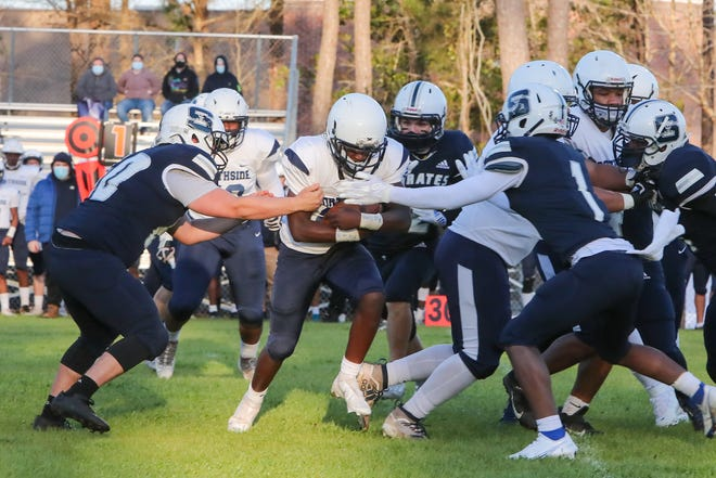 Northside's Dennis Mingledoff tries to break tackles Friday in the Monarchs' 21-7 win at Swansboro on Friday.