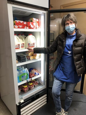Lynn Grubbs, who helps operate the food pantry and retail shop at the Volunteers of America in Aurora, displays some of the parishable foods the Knights of Columbus at Our Lady of Perpetual Help Church were able to provide because of a recent successful kettle corn sales season.