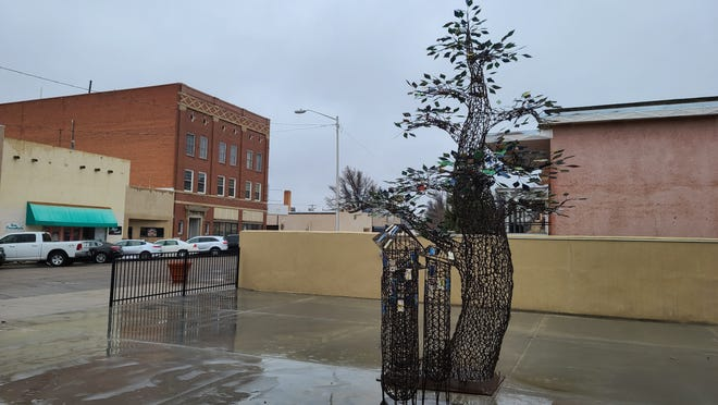 Despite drizzles of rain and early morning flakes of snow, the 'Wishing Tree' installed at Livewell Park on Third Street and Santa Fe Avenue stands out among a gray backdrop with green, glinting metal leaves on Friday, March 19, 2021.