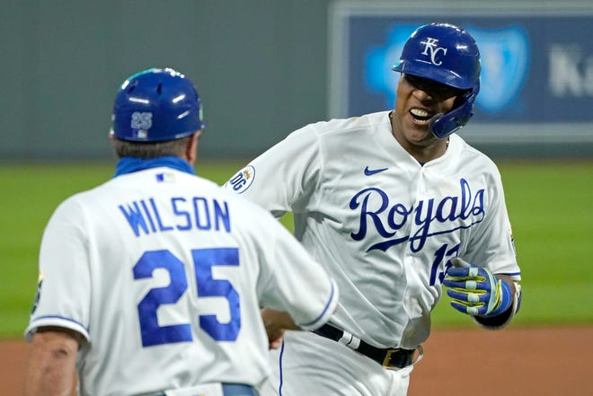 FILE - In this  Thursday, Sept. 24, 2020 file photo, Kansas City Royals' Salvador Perez celebrates with third base coach Vance Wilson after hitting a three-run home run during the first inning of the team's baseball game against the Detroit Tigers in Kansas City, Mo.