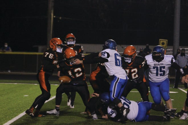 Macomb's Jack Duncan looks to escape a B/WP tackler.