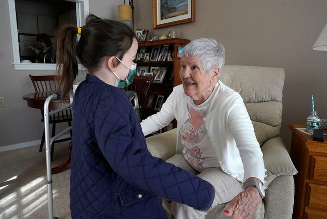 Eileen Quinn, 98, right, a resident at New Pond Village retirement community, in Walpole, Mass., greets her great-granddaughter Maeve Whitcomb, 6, of Norwood, Mass., left, on March 21 at the retirement community, in Walpole. Quinn said it was the first time she had been able to visit with her great-grandchildren in her apartment since the coronavirus pandemic began. (AP Photo/Steven Senne)