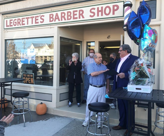"""Canandaigua Mayor Bob Palumbo presents a proclamation declaring March 22 as """"Jack LeGrette Day"""" on the 50th anniversary of the Niagara Street business."""
