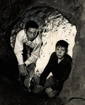 "Brothers Ora Lee and Jerry Don Linville played hooky from Southeast High School for more than six months in 1957, spending their school hours in a cave they had dug into a nearby creek embankment. The ruse was over, though, when police discovered the pair sitting by a campfire next to the cave. Their parents were unaware the boys had been skipping school, but after a ""pretty hard talking to"" by their father, they were in school the next day. This photo was published March 28, 1957, on the front page of The Daily Oklahoman."