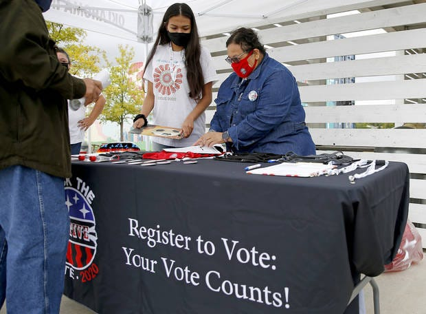 Codie Topetchy, left, and Roxanna Foster with Rock the Native Vote, help a man register to vote Sept. 22, 2020, during a voter registration drive put on by Rock the Native Vote, Voto Latino and the Oklahoma City Thunder to celebrate National Voter Registration Day at the Wheeler Ferris wheel in Oklahoma City.
