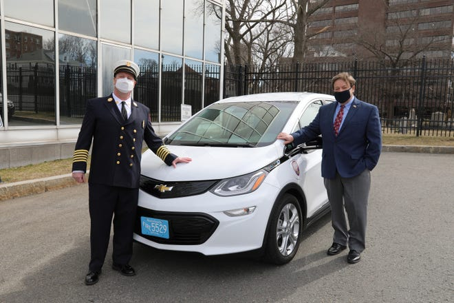 Quincy Fire Chief Joe Jackson, left, and Mayor Thomas Koch pose with the city's first electric vehicle.