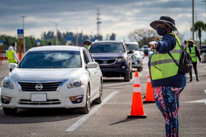 Cars line up as people come for the Pfizer COVID-19 vaccine at the South Florida Fairgrounds in Palm Beach County, Florida on March 22, 2021.
