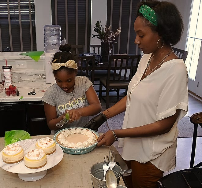 Zianna Golden, 9, zests a lime under her mother's watchful eye. Zianna is one of three of Oh My Yum! Owner Jasmine Golden's daughters who help out the business.