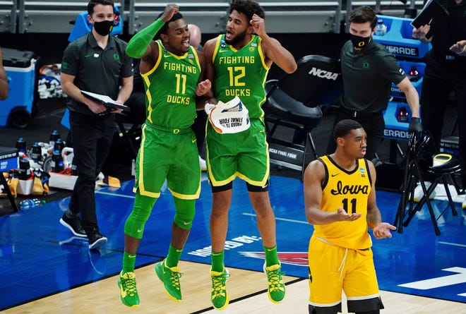 Oregon's Amauri Hardy (11) and LJ Figueroa (12) celebrate a second-half play in the Ducks' 95-80 win over Iowa on Monday as Hawkeyes guard Tony Perkins looks on.
