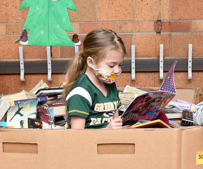 Genoa Elementary School first-grader Kali D'Elia looks over donated books from the Cleveland Kids' Book Bank. The donated books will be given out to students at the end of the school year. Genoa Principal Mandy Gardinsky wants to ensure that every student has books to read at home.