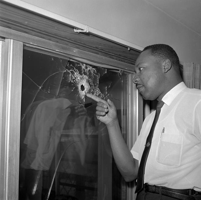 Martin Luther King Jr. points to a bullet hole in a glass sliding door of a home he was scheduled to stay in on Atlantic View in Butler Beach, south of St. Augustine, after it was shot at in 1964. King was not in the home at the time.