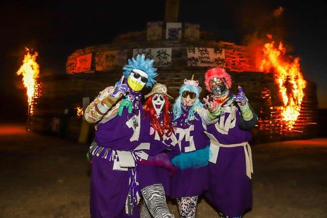 Members of the Purple Poo show their Texans spirit during Friday's L.V. Risinger Memorial Bonfire.