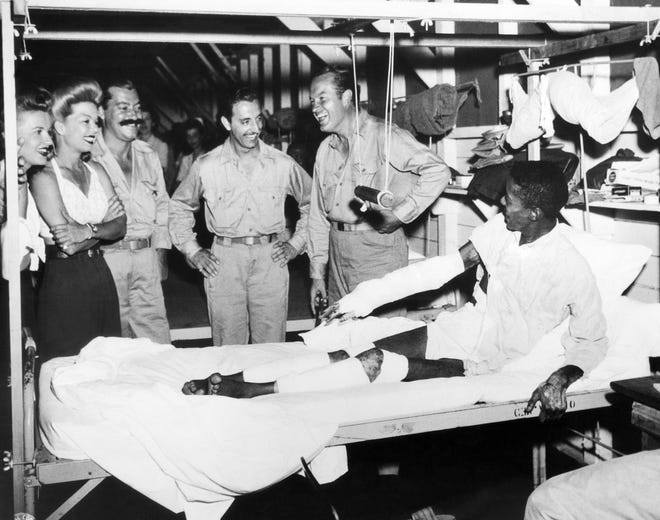 Bob Hope, second from right, laughs at a joke told by S/Sgt. Johnnie Tubbs of Dallas, Tex., in a hospital in October 1944. Hope frequently visited military members in hospitals. With them, are, from left, dancer Patty Thomas, singer Frances Langford; singer and comedian Jerry Colonna and guitarist Ton Romano