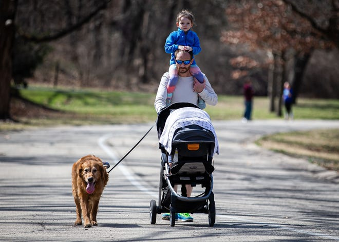 Tinley Gabelmann, 3, hitches a ride on the shoulders of her father, Jeremy Gabelmann, as he pushes her 2-month old brother Rowan Gabelmann, while holding on to Wrigley, a golden retriever, on a walk in Washington Park in Springfield March 22.