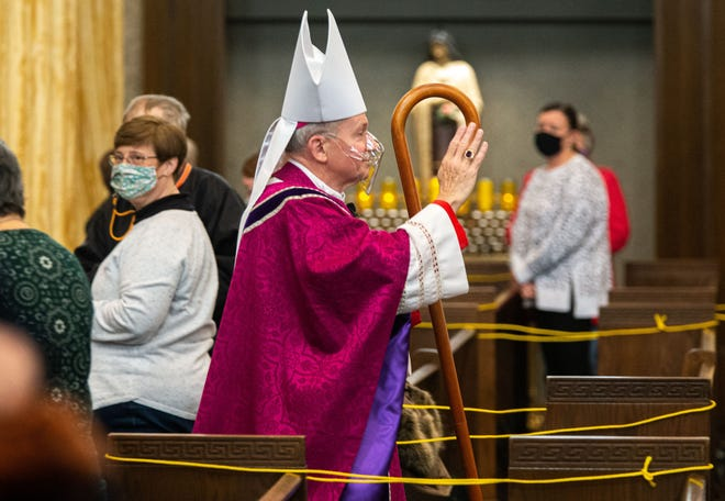 Bishop Thomas John Paprocki wears a clear face mask during the COVID-19 pandemic as he processes out of the sanctuary following mass during Ash Wednesday at the Cathedral of the Immaculate Conception in Springfield, Ill., Wednesday, February 17, 2021. The yellow ropes block off access to every other row of pews to maintain social distancing during the COVID-19 pandemic.