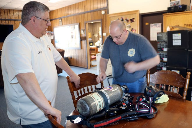 Haring Township Fire Chief Duane Alworden, left, and Deputy Chief Keith Ball talk as Ball does an equipment check on a new air pack the department received, March 12, 2021 in Haring Township, Mich. Mutual aid with neighboring communities has remained an important part of local fire departments and will continue to be as the recruitment of new firefighters becomes more difficult. (Rick Charmoli /The News via AP)